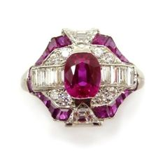 Ruby and diamond cluster ring by Cartier, centered by a cushion-cut ruby to a shaped hexagonal surround set with baguette, trapezium and by madge (=)