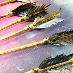 Arrows DIY. Stained wooden dowels; cut up a bit with knife to look like branches. Cut real feathers in half and glued them to the end of the dowel and wrap w/ leather.