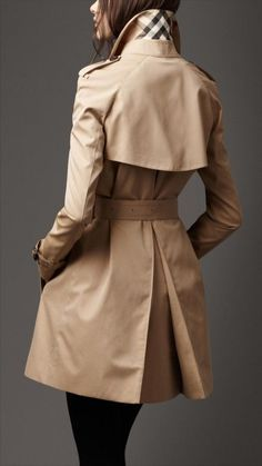 Burberry A-line trench coat.Back rain shield, elongated central back pleat. Trademark leather buckles, check under collar.