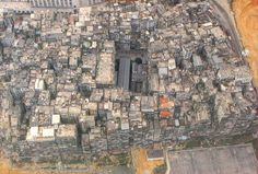 Kowloon Walled City [KWC] - China  demolished in 1992.   33,000 families and businesses living in more than 300 interconnected high-rise buildings, all constructed without contributions from a single architect.