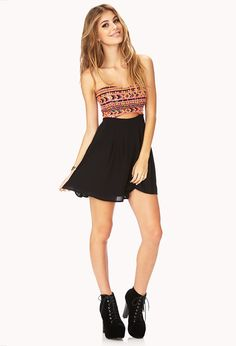 A chiffon dress featuring a sequined tribal pattern bodice and cutout waist; tube top and pleated waist.