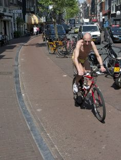 You know the weather in Amsterdam is lovely whenever this exhibitionist takes to the streets on his bike...