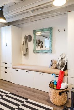 entrée moderne et blanche aménagée avec un banc avec rangements, un meuble colonne et un miroir vintage comme accent
