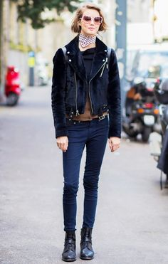 Lindsey Wixson wears a black shirt, cardigan, furry motorcycle jacket, skinny jeans, lace-up boots, a neckerchief, and retro sunglasses
