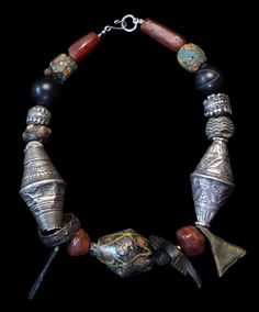 by Marion Hamilton | Ancient carnelian followed by Roman ear green glass bead, contemporary agate, 19th century silver Yemeni, Roman glass, silver Afghani, Hittite bronze ring on left, 19th century brass amulet Nigeria on right, rare Byzantine glass bead in center || 4'500$