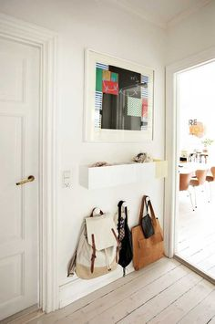 Small white entryway landing strip with wall-mounted storage and hooks