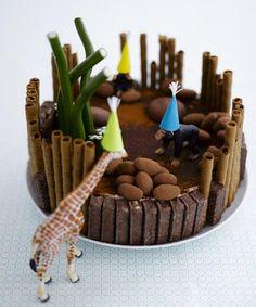 ¡¡ Fiesta en el zoo !! Una estupenda tarta de chocolate.  Aquí se le han añadido galletas para confeccionar la jaula y en forma de piedras se han colocado las buenísimas almendras chocolateadas, irresistible. Mirad la vegetación con chuches de regaliz verde.