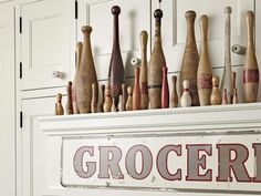 "Wooden Pin Display: A ledge above the stove holds a collection of vintage bowling and juggling pins. The antique ""groceries"" sign fit the space as-is."