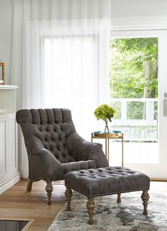 In front of glass patio doors covered in sheer white curtains, a a gray tufted reading chair with a matching ottoman sits catty corner on a gray rug beside a round brass tray accent table.