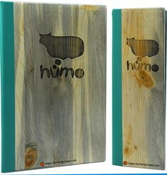 Environmentally responsible menu in solid blue pine, coach faux leather quarterbind spine in a soft teal green that wraps around to cover the back cover.  The decoration is laser-engraved artwork that has a dark stain to accentuate the design.