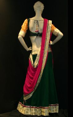 Black cotton silk blouse with brocade sleeves worn over dark green color georgette skirt with brocade border matched with bright pink georgette  dupatta.