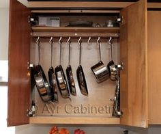 particularly useful if hooks can slide along a track on the inside of the cabinet so that they can be 'nested' and slid side to side to access any given pot...