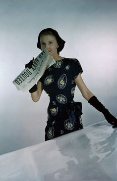 1945 Model is wearing a print dress with a black ground made of rayon crepe by Larry Aldrich.