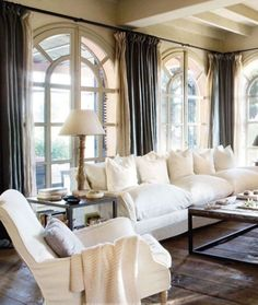 natural light; arched windows; curtains; wooden floors; white couches