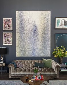 Large statement art teams with a shimmering silver Chesterfield and dark grey…