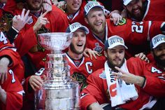 Chicago Blackhawks center Jonathan Toews poses with teammates and the Stanley Cup Monday in the United Center in Chicago.