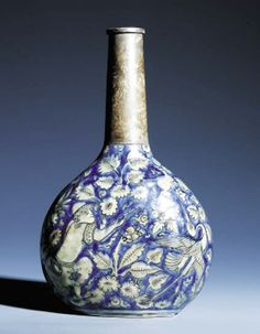 "A SAFAVID BLUE & WHITE MOULDED SOFT PASTE PORCELAIN BOTTLE PROBABLY MESHED, SOUTH EAST PERSIA, FIRST HALF 17TH CENTURY With rounded body flattened on each side rising to a tubular neck, body moulded & left in reserve against the blue glaze with a design of a proliferation of trees and flowering shrubs together with perching birds around the figure of a European & his diminutive woman on one side & a hunter shooting at a deer on the other, neck now missing & replaced with white metal, 13"" H"