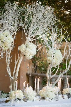 Branches, hydrangea, and crystals make up beautiful white centerpieces. Perfect for a winter wedding!