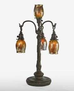 Tiffany Studios FOUR-LIGHT TABLE LAMP each shade engraved L.C.T. base impressed 29723/TIFFANY STUDIOS/NEW YORK with the Tiffany Glass and Decorating Company monogram favrile glass and patinated bronze 29 1/2  in. (74.9 cm) high