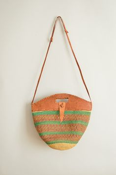 Vintage Kenyan Kiondo. Made by hand from woven sisal and leather. It has a long, adjustable strap that can be worn at the shoulder, across the chest or