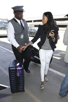 Zoe Saldana wearing a cute spring outfit: White distressed skinny jeans, black and white print flats, a striped shirt and a pinstripe blazer