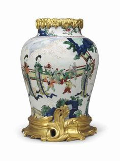 A LOUIS XV ORMOLU-MOUNTED CHINESE WUCAI PORCELAIN BALUSTER VASE THE ORMOLU CIRCA 1750, THE PORCELAIN CIRCA 1650 The porcelain with scenes of courtly ladies in a landscape, the rim and foot applied with rocaille-cast mounts 15 in. (38 cm.) high
