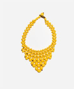 This beautiful bib necklace is crafted from artfully draped layers of handmade paper beads.