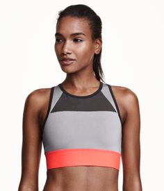 Fully lined, color-block sports bra in fast-drying, breathable functional fabric. High neckline at front, racer back with cut-out section, ventilating mesh panels, and wide elastication at lower edge. Medium support.
