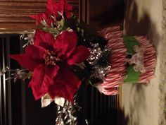 Candy canes around a cylinder vase & poinsettias to decorate !