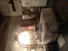 Beautiful old bed with iron garden archway above. Lighted chandelier hanging above.