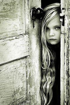 Little Girl peeking through an old door.