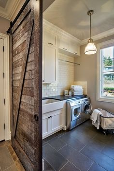 Rustic laundry room featuring a sliding barn door, gray tile floors, stainless steel appliances, white subway tiles and a classic farmhouse sink | Garrison Hullinger