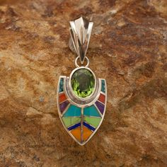 This beautiful Sterling Silver Pendant, as part of the Indian Summer Collection, features Red & Orange Spiny, Sugilite, Gaspiete, AZ Blue Turquoise, Lapis & Campitos Turquoise with Green Peridot. Dime