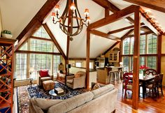 By no means big, the second-floor living area in this New Hampshire timber home is still large enough for entertaining a crowd. Photo courtesy of Yankee Barn Homes.