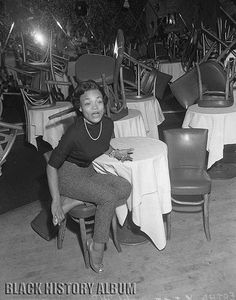Singer Eartha Kitt, seated in empty nightclub in Los Angeles, CA, 1953. Los Angeles Times photographic archive, UCLA Library. Copyright Regents of the University of California, UCLA Library. This work is licensed under a Creative Commons Attribution-Noncommercial-Share Alike 3.0 United States License.