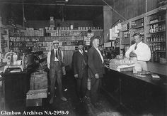 Title: Interior of grocery store, Calgary, Alberta. Date: 1906 Remarks: Owned by Luke Draper, located 226 - 17th Avenue SW in Victoria Park district. L-R: Sidney Blight, delivery man; Dick Tennant; ---?; Luke Draper. The store was demolished in 2008.