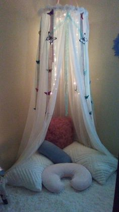 I created my own little meditation area in a corner of my room. I made the mosquito net with ribbon from the Dollar Tree and Hobby Lobby, embroidery hoop, 3 sheer curtain panels from Dirt Cheap, Christmas lights, and all the pillows and shams came from a thrift store, which I washed. I added some stuffing from an old pillow to the boppie pillow to make my own Crescent zafu meditation pillow for $3. .. and finally a big fuzzy rug and some new candles from Ross.