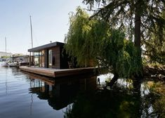 A dark exterior contrasts with light-toned finishes inside a compact, floating home in Washington designed by Studio DIAA co-founder Suzanne Stefan as her own home. The Portage Bay Float Home serves as the personal residence of Stefan, who co-founded Studio DIAA in 2019. The project recently won a 2021 Housing Award from the American Institute of Architects.