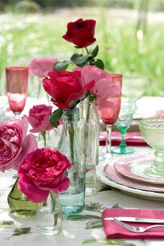 .Ao ar livre uma mesa posta com flores, dá um toque especial