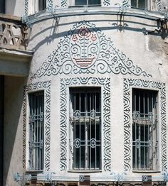 Hungary, Tatabánya, former club of Magyar Általános Kőszénbánya Rt. (Hungarian General Coal Mines Co.) People call it Tulip House after the stylized Hungarian-Transylvanian folk motifs in the ornamentations. Built in 1922, architect: Ede Torockai Wigand and Béla Jánszky. Torockai Wigand created a unique synthesis of Art Nouveau, Hungarian rural architecture and modern building technologies in the early 20th century. Art Nouveau Illustration, Coal Mining, Modern Buildings, Art And Architecture, Louvre, Windows, Club, Travel, City Landscape