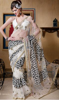 This white and black net and viscose dual fabric saree is beautifully designed with geometric print, resham, sequins, mirror and patch work done in form of geometric and paisley motiff. All over embroidered patch patti border is enhancing the beauty