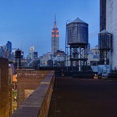 Wtny. Water tower at dusk with Empire State Building in background. NYC