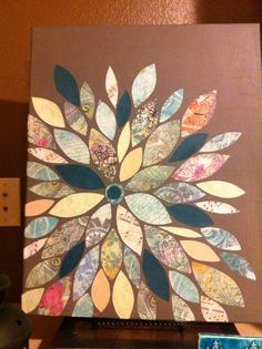 "My attempt at a scrapbook canvas picture. Used 6 different scrapbook papers on A 16x22 canvas from Michaels. Painted the canvas in a grey base color and used Elmer's glue to put the cut out ""petals"" on the canvas. Home made Modge podge (half glue and water) and you are done! Total cost $3."