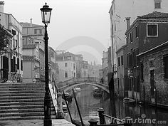 Black and white image of venice canal in the rain and mist.