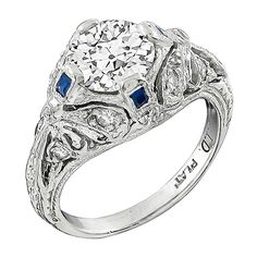 Art Deco 1.05 Carat GIA Cert Diamond Platinum Engagement Ring. This gorgeous platinum engagement ring from the Art Deco era, centers a sparkling GIA certified old mine cut diamond that weighs 1.05ct. The color of the diamond is I with VS2 clarity. The center diamond is accentuated by dazzling round cut diamond and square cut sapphire accents.