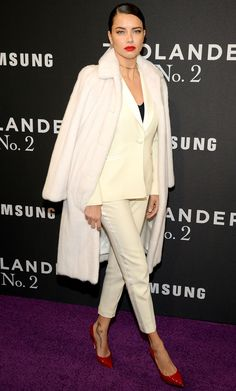 ADRIANA LIMA in a furry white coat draped over a cream suit paired with red pumps and a Jennifer Fisher chokcer at the Zoolander 2 premiere in N.Y.C.