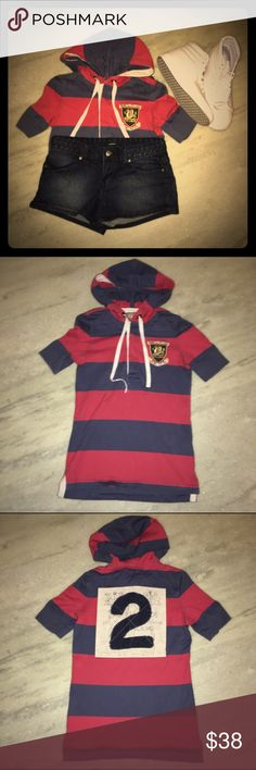"""Authentic Ralph Lauren Rugby Shirt Authentic Ralph Lauren Rugby Shirt in excellent condition. I've only worn this once or twice. Shirt has blue and red vertical stripes with hidden button up closure in the front. There is also a dragon emblem on the left breast with the words """"Game to the last, look well play well"""" written above/under it. The back of the shirt has the #2 on top of a cream colored backsplash. The shirt is has a hood with adjustable drawstrings and cap sleeves. Super soft…"""