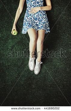 Teenage girl lying on the grass, she is relaxing and eating an apple, top view - Shutterstock Premier