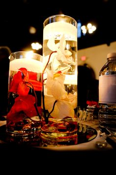 Center pieces with candles lit - Red/Ivory artificial orchids in water with floating candles and red/clear glass gems