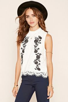 A knit top featuring a crochet lace design with floral embroidery, a mock neck, keyhole back, scalloped eyelash lace trim, and a sleeveless cut. #thelatest